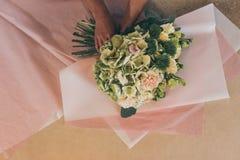 Ανθοκόμος που τακτοποιεί τα όμορφα λουλούδια στο έγγραφο τεχνών Στοκ φωτογραφίες με δικαίωμα ελεύθερης χρήσης