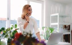 Ανθοκόμος που χρησιμοποιεί το κινητό τηλέφωνο στο ανθοπωλείο της Στοκ Εικόνα
