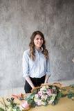 Ανθοκόμος στην εργασία: αρκετά νέα γυναίκα που κάνει τη μόδα τη σύγχρονη ανθοδέσμη των διαφορετικών λουλουδιών Στοκ Εικόνα