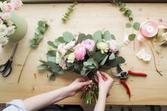 Ανθοκόμος στην εργασία: αρκετά νέα γυναίκα που κάνει τη μόδα τη σύγχρονη ανθοδέσμη των διαφορετικών λουλουδιών Στοκ Φωτογραφίες