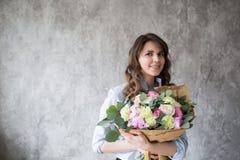Ανθοκόμος στην εργασία: αρκετά νέα γυναίκα που κάνει τη μόδα τη σύγχρονη ανθοδέσμη των διαφορετικών λουλουδιών Στοκ εικόνα με δικαίωμα ελεύθερης χρήσης
