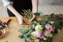 Ανθοκόμος στην εργασία: αρκετά νέα γυναίκα που κάνει τη μόδα τη σύγχρονη ανθοδέσμη των διαφορετικών λουλουδιών Στοκ Φωτογραφία