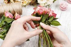 Ανθοκόμος στην εργασία Γυναίκα που κάνει την ανθοδέσμη των ρόδινων τριαντάφυλλων Στοκ Φωτογραφίες