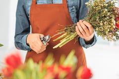 Ανθοκόμος στην εργασία: τα θηλυκά χέρια της γυναίκας που κάνει τη μόδα τη σύγχρονη ανθοδέσμη των διαφορετικών λουλουδιών Στοκ Εικόνα