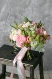 Ανθοδέσμη άνοιξη των μικτών λουλουδιών στο εκλεκτής ποιότητας γκρίζο υπόβαθρο τοίχων πίσω Στοκ Φωτογραφία