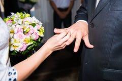 Ανθοδέσμη λαβής νυφών και νεόνυμφων των λουλουδιών με τα δαχτυλίδια Στοκ Εικόνες