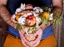 Ανθοδέσμη από τα λουλούδια και φρούτα στα χέρια η σύνθεση κεριών φθινοπώρου μήλων ξηρά βγάζει φύλλα vase απόλυσης Στοκ Εικόνες
