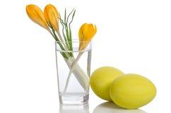 Ανθοδέσμη από τα λουλούδια κρόκων στο βάζο και τα αυγά Πάσχας Στοκ εικόνα με δικαίωμα ελεύθερης χρήσης