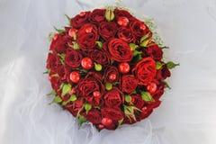 Ανθοδέσμη γαμήλιων δεσμών των κόκκινων τριαντάφυλλων στο πέπλο Στοκ Εικόνα
