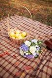 Ανθοδέσμη γαμήλιων λουλουδιών και καλάθι των κίτρινων οργανικών μήλων και Στοκ Φωτογραφίες