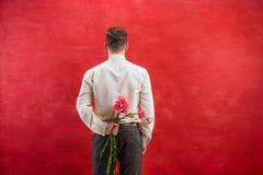 Ανθοδέσμη εκμετάλλευσης ατόμων των γαρίφαλων πίσω από την πλάτη Στοκ Εικόνες