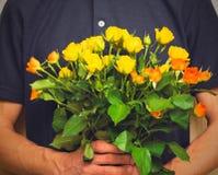 Ανθοδέσμη εκμετάλλευσης ατόμων των κίτρινων και πορτοκαλιών τριαντάφυλλων Ημέρα Women s, Va Στοκ Εικόνες