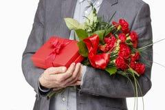 Ανθοδέσμη εκμετάλλευσης ατόμων των λουλουδιών γαρίφαλων και του κόκκινου κιβωτίου με το μεγάλο BO Στοκ εικόνα με δικαίωμα ελεύθερης χρήσης