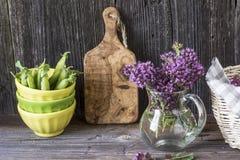 Ανθοδέσμη ζωής κουζινών ακόμα ανθίζοντας oregano, νέα πράσινα μπιζέλια λοβών στα κεραμικά κύπελλα σε ένα απλό ξύλινο υπόβαθρο Στοκ φωτογραφίες με δικαίωμα ελεύθερης χρήσης