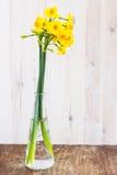Ανθοδέσμη κίτρινου που παραχωρεί lilly (daffodil) σε μια ξύλινη επιφάνεια Στοκ Φωτογραφία
