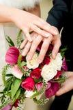 Ανθοδέσμη και χέρια με τα δαχτυλίδια Στοκ Εικόνες
