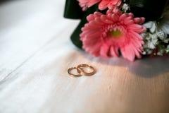 Ανθοδέσμη και δύο γαμήλια δαχτυλίδια Στοκ Εικόνες