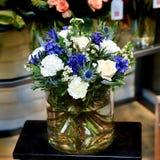 Ανθοδέσμη με τα άσπρα και μπλε λουλούδια σε ένα βάζο γυαλιού Στοκ Εικόνες
