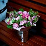 Ανθοδέσμη με τα ιώδη λουλούδια και τα ρόδινα τριαντάφυλλα σε έναν κάδο σιδήρου Στοκ Εικόνες