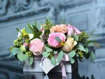 Ανθοδέσμη με τα μπεζ τριαντάφυλλα και τα ρόδινα peonies σε ένα γκρίζο κιβώτιο Στοκ Φωτογραφίες