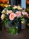 Ανθοδέσμη με τα ρόδινα τριαντάφυλλα και τα κίτρινα λουλούδια σε ένα βάζο γυαλιού Στοκ Φωτογραφίες