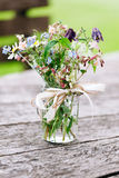 Ανθοδέσμη λουλουδιών στο βάζο γυαλιού στο αγροτικό ξύλινο υπόβαθρο Στοκ φωτογραφίες με δικαίωμα ελεύθερης χρήσης