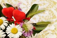 Ανθοδέσμη λουλουδιών wid και δύο καρδιών στο υπόβαθρο τσιγγελακιών στοκ εικόνα