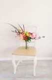 Ανθοδέσμη στην εκλεκτής ποιότητας καρέκλα Στοκ Φωτογραφίες