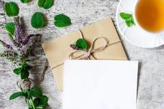 Ανθοδέσμη των άγριων λουλουδιών με τη ευχετήρια κάρτα και φλυτζάνι του τσαγιού Στοκ Εικόνες