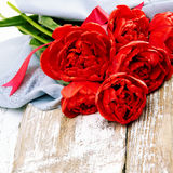 Ανθοδέσμη των κόκκινων φρέσκων λουλουδιών τουλιπών άνοιξη στο παλαιό ξύλινο backgrou Στοκ Φωτογραφία