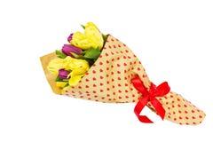 Ανθοδέσμη των λουλουδιών άνοιξη που τυλίγονται στο έγγραφο με τις καρδιές, που διακοσμούνται με την κόκκινη κορδέλλα απομονωμένος Στοκ Φωτογραφία