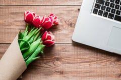 Ανθοδέσμη των λουλουδιών και ο φορητός προσωπικός υπολογιστής σε έναν πίνακα Στοκ Εικόνες