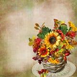 Ανθοδέσμη των λουλουδιών, των φύλλων και των μούρων φθινοπώρου σε ένα ψάθινο καλάθι σε ένα εκλεκτής ποιότητας υπόβαθρο Στοκ φωτογραφία με δικαίωμα ελεύθερης χρήσης