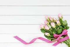 Ανθοδέσμη των ρόδινων τριαντάφυλλων που διακοσμούνται με την κορδέλλα στο άσπρο ξύλινο υπόβαθρο Τοπ όψη Στοκ Φωτογραφίες
