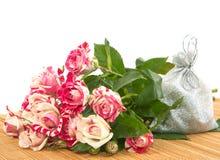 Ανθοδέσμη των τριαντάφυλλων και ένα δώρο στο υπόστρωμα. Στοκ Φωτογραφίες
