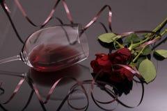 Ανθοδέσμη των τριαντάφυλλων και του κόκκινου κρασιού γυαλιού στο Μαύρο Στοκ φωτογραφία με δικαίωμα ελεύθερης χρήσης