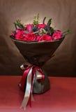 Ανθοδέσμη των τριαντάφυλλων που τυλίγονται στο καφετί έγγραφο και που δένονται με τις κορδέλλες Στοκ Φωτογραφία