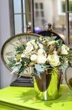 Ανθοδέσμη των τριαντάφυλλων σε έναν λαμπρό κάδο μετάλλων σε έναν πράσινο πίνακα Στοκ Φωτογραφίες