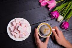 Ανθοδέσμη των τρυφερών ρόδινων τουλιπών και των χεριών που κρατούν το φλιτζάνι του καφέ Στοκ Εικόνα