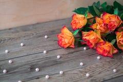Ανθοδέσμη των όμορφων πορτοκαλιών τριαντάφυλλων σε ένα ξύλινο υπόβαθρο και διεσπαρμένες χάντρες των μαργαριταριών Στοκ Φωτογραφίες