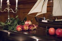 Ανθοδέσμη των όμορφων τριαντάφυλλων, πρότυπο sailboat και δύο μήλων σε ένα β Στοκ εικόνα με δικαίωμα ελεύθερης χρήσης
