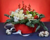 Ανθοδέσμη Χριστουγέννων των τριαντάφυλλων και των κλάδων έλατου σε ένα κόκκινο κιβώτιο Στοκ Φωτογραφίες