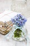 Ανθοδέσμη forget-me-not των λουλουδιών στο βάζο γυαλιού, σωρός του τρύού Στοκ Εικόνα