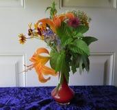 Ανθοδέσμη Wildflowers στο μικρό κόκκινο βάζο γυαλιού & κίτρινες Daylilies & την πρασινάδα Στοκ φωτογραφία με δικαίωμα ελεύθερης χρήσης