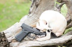 Ανθρώπινα πρότυπο και πυροβόλο όπλο κρανίων στο κούτσουρο Στοκ Εικόνες