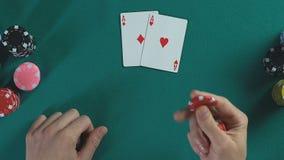 Ανθρώπινα τσιπ πόκερ εκμετάλλευσης χεριών, ζευγάρι των καρτών άσσων, αρσενικό που σκέφτονται για το στοίχημα απόθεμα βίντεο