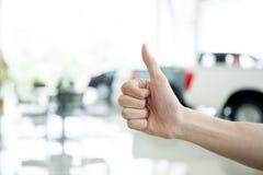 Ανθρώπινα χέρια που δίνουν τους αντίχειρες επάνω με το κλειδί αυτοκινήτων στο αυτοκίνητο shoowroom Στοκ φωτογραφία με δικαίωμα ελεύθερης χρήσης