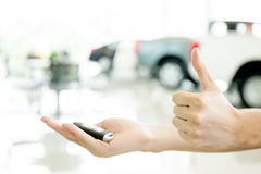 Ανθρώπινα χέρια που δίνουν τους αντίχειρες επάνω με το κλειδί αυτοκινήτων στο αυτοκίνητο shoowroom Στοκ Φωτογραφίες