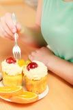 Ανθρώπινα χέρια που καρφώνουν το γλυκό κέικ κρέμας με τη διχάλα gluttony Στοκ Εικόνες