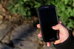 Ανθρώπινα χέρια που κρατούν ένα smartphone και που παίζουν το παιχνίδι ή το σε απευθείας σύνδεση soci Στοκ φωτογραφίες με δικαίωμα ελεύθερης χρήσης